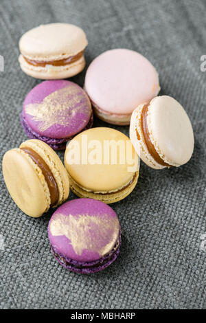 Close-up colorful French or Italian macaron on white wooden table. Macarons is French dessert served with tea or coffee. wallpaper, Vertical photo - Stock Photo
