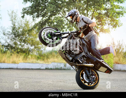 Ivano-Frankivsk, Ukraine - 28 August 2015 : Young biker is showing his talents of doingdangerous tricks on his sport motorcycle. He is riding on summer city street. - Stock Photo