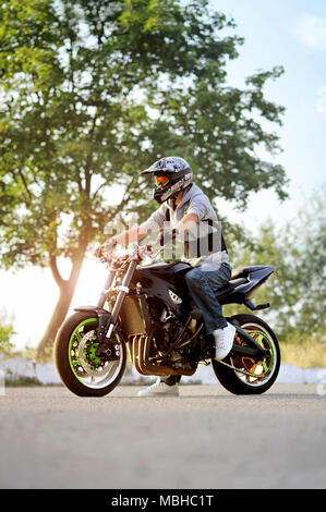 Ivano-Frankivsk, Ukraine - 28 August 2015 : young male biker sitting on motorcycle on summer city street. wearing protective helmet. looking impressive and confident. - Stock Photo