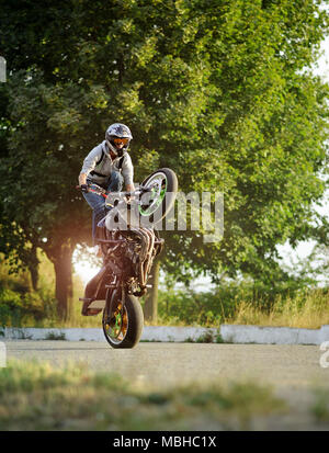 Ivano-Frankivsk, Ukraine - 28 August 2015 : Young male biker is showing his talents in extreme riding and making tricks on one cycle on summer city street. Man wearing protective helmet. - Stock Photo