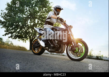 Ivano-Frankivsk, Ukraine - 28 August 2015 : Photo of biker, wearing protective helmet is sitting on his colorful sport motorcycle standing on summer road, filled with shine of sunset. - Stock Photo
