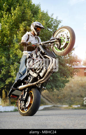 Ivano-Frankivsk, Ukraine - 28 August 2015 : Amazing sideview of practising extreme motorcycle trick biker. Man showing off his talents riding on the street during summer sunny evening. - Stock Photo