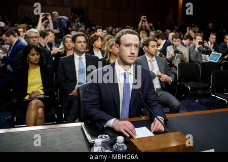 Washington, USA. 10th Apr, 2018. Facebook CEO Mark Zuckerberg (C) testifies at a joint hearing of the Senate Judiciary and Commerce committees on Capitol Hill in Washington, DC, United States, on April 10, 2018. Facebook CEO Mark Zuckerberg told Congress in written testimony on Monday that he is 'responsible for' not preventing the social media platform from being used for harm, including fake news, foreign interference in elections and hate speech. Credit: Ting Shen/Xinhua/Alamy Live News - Stock Photo