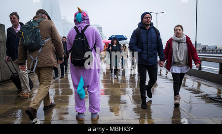 London, UK. 11th April 2018. UK Weather: A fundraiser for the Meningitis Research Foundation stands on London Bridge as passing commuters make their way to work on a drizzly day in the capital (c) Paul Swinney/Alamy Live News - Stock Photo