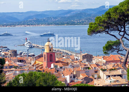 Panoramic view of Saint Tropez, Mediterranean chic fishing village in French Riviera, over roofs of old historical houses, port pier with super yachts - Stock Photo