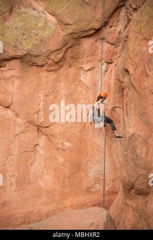 Rock Climber woman rappeling down descending sandstone cliffs on belay in Garden of The Gods in Colorado Springs, Colorado, USA, April 4, 2016