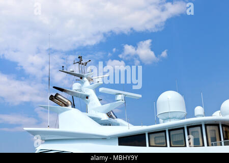 Top of super yacht with radars, antenna against cloudy blue sky . - Stock Photo