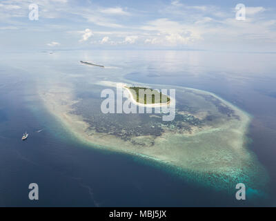 A Pinisi schooner drifts near a remote, tropical island in the Banda Sea. This region is in the Coral Triangle and has high marine biodiversity. - Stock Photo
