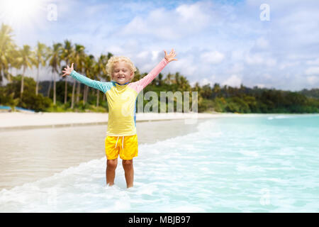 Child on beautiful beach. Little boy with toy boat running and jumping at sea shore. Ocean vacation with kid. Children play on summer beach. Water fun - Stock Photo