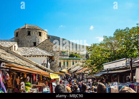 Tourists crowd the main street through Old Town Mostar, Bosnia and Herzegovina as they pass by shops with souvenirs and gifts - Stock Photo