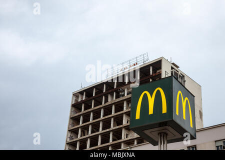 BELGRADE, SERBIA - MARCH 31, 2018: Mc Donald's logo with its iconic M in front of a half destroyed building in downtown Belgrade  Picture of a Mc Dona - Stock Photo