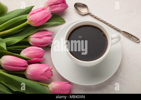 Black coffee in white Cup with pink tulips on light stone background. Top view - Stock Photo