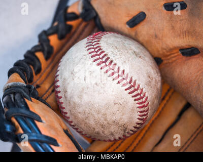 Close up sports background image of an old used weathered leather baseball with red laces inside of a baseball glove or mitt showing intricate details - Stock Photo