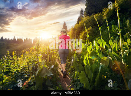 Beautiful sporty girl in pink shirt walking in the mountain trail at cloudy sunset sky - Stock Photo