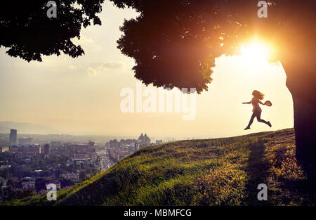 Woman in silhouette running with hat in her hand at the sunset city view background. City life concept. - Stock Photo
