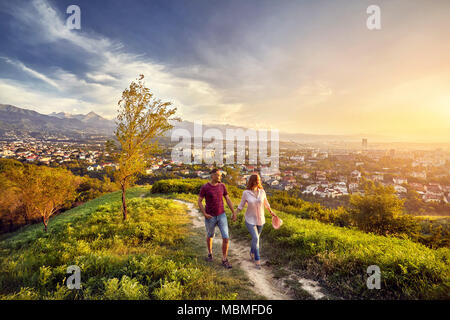 Yong couple in pink clothes walking in the park at the sunset city view background. - Stock Photo