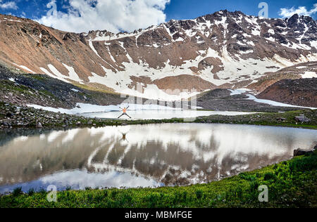 Hiker in orange shirt jumping with rise hand near lake in the snowy mountains - Stock Photo