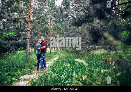 Young hipster couple in checkered shirt hugging in the pine tree forest. Love in the nature. - Stock Photo