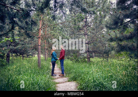 Young hipster couple in checkered shirt holding each other by hand in the pine tree forest. Love in the nature. - Stock Photo