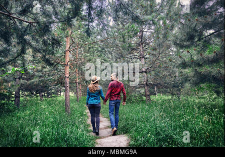 Young hipster couple in checkered shirt holding by hands and walking in the pine tree forest. Love in the nature. - Stock Photo