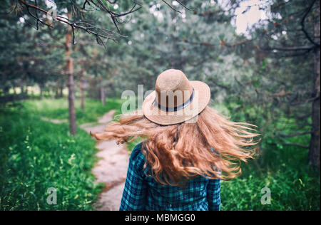 Young woman in brown hat and green checked shirt with long hair flow in the wind under pine tree in the forest - Stock Photo