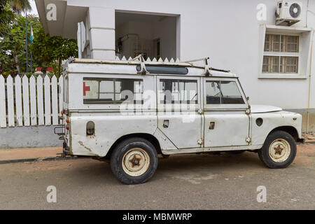 A Well used Ambulance Landrover Defender parked on a side street beside a Clinic on the Island of Sao Tome in West Africa one afternoon. - Stock Photo