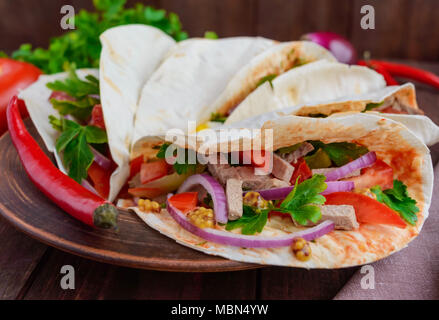 East pita bread with various fillings (meat, salami, egg, cucumber, parsley, tomato, chili pepper, Dijon mustard). Taco. - Stock Photo