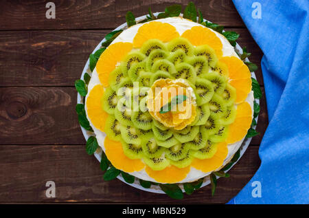 Bright round festive fruit cake decorated with kiwi, orange, mint. The top view. - Stock Photo