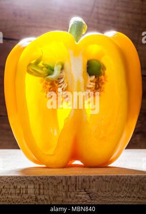 Still life shot of a partially cut open yellow bell pepper.