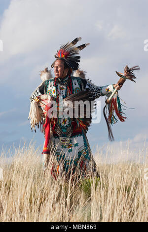 Native American man wearing traditional Cheyenne costume, dancing on the plains - Stock Photo