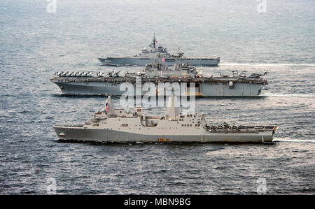 180409-N-NM806-1083  EAST CHINA SEA (April 9, 2018) The forward-deployed amphibious transport dock ship USS Green Bay (LPD 20), front, the forward-deployed amphibious assault ship USS Wasp (LHD 1), and the Japan Maritime Self-Defense Force Osumi-class amphibious transport dock ship JS Shimokita (LST 4002) maneuver together as part of a coordinated formation. The bilateral navigational maneuvers were conducted as part of an enduring commitment of both sea services to increase U.S.-Japan naval interoperability. (U.S. Navy photo by Mass Communication Specialist 3rd Class Taylor King/Released) - Stock Photo