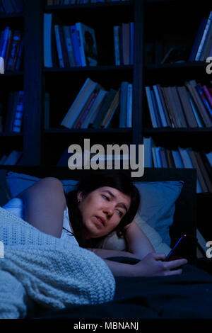 Portrait of woman with phone lying in bed at night - Stock Photo