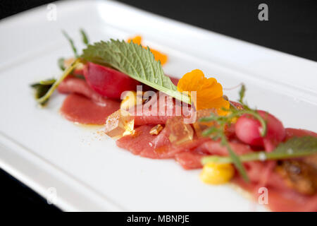 closeup of a plate of thin slices of raw meat with fresh flowers, rocket salad and white wine yelly cubes - Stock Photo