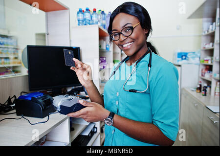 African american pharmacist working in drugstore at hospital pharmacy. African healthcare. Work with payment terminal and credit card. - Stock Photo