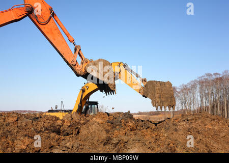 Construction of moorings for the parking of boats - Two Excavators work in dirt - Stock Photo