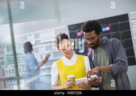 Creative business people using smart phone and digital tablet in office - Stock Photo