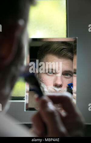 Reflection of handsome man with green eyes shaving with blue razor in small mirror