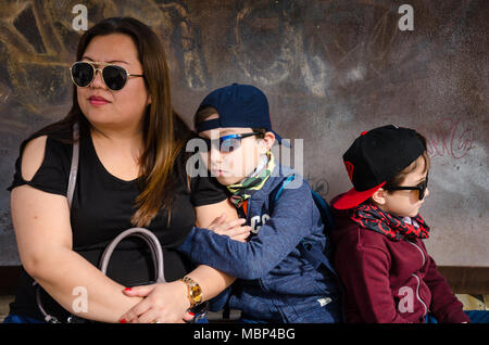 A mother sits and waits with her two young children for a train while on holiday in Spain. - Stock Photo