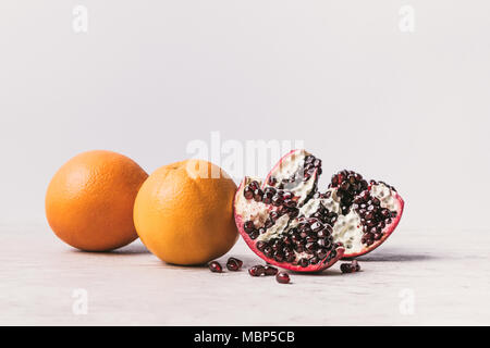 ripe delicious oranges and pomegranate on marble surface - Stock Photo