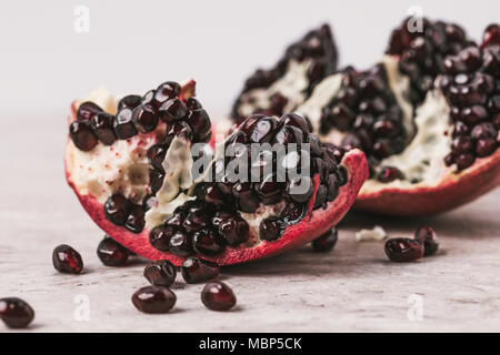 close up view of ripe appetizing pomegranate on marble table - Stock Photo