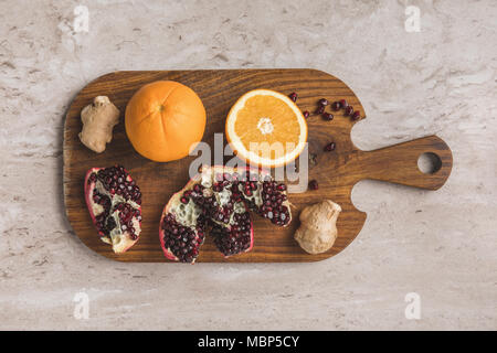 top view of oranges, pomegranate and ginger on cutting board  - Stock Photo