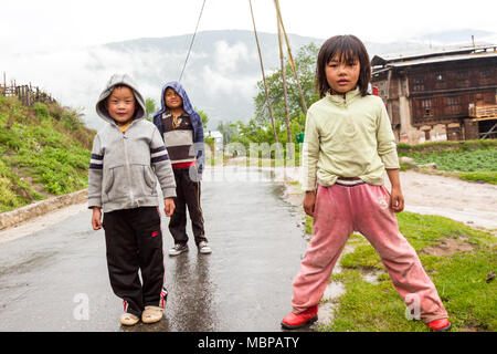 Bhutanese children playing on road seen on the road trip to Bhutan in Himalayas - Stock Photo