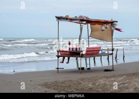Man sitting on a traditional persian sea bench along the Caspian coast. Nur, Iran - Stock Photo