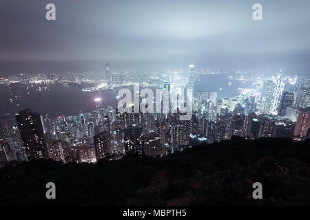 Skyline of Hong Kong and the Victoria Harbour seen from Victoria Peak on Hong Kong Island, SAR of China - Stock Photo