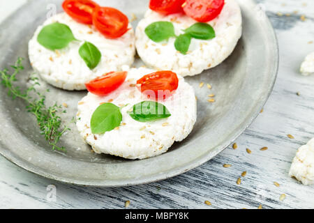 Healthy Rice Cakes with cherry tomatoes, cheese feta, basil and sesame in metal plate on white background. Diet snack. - Stock Photo