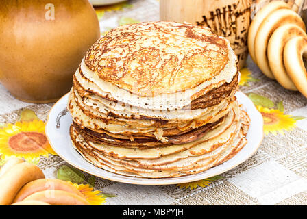 Russian traditional food. Stack of appetizing fried pancakes on the table during Pancake Week - Stock Photo