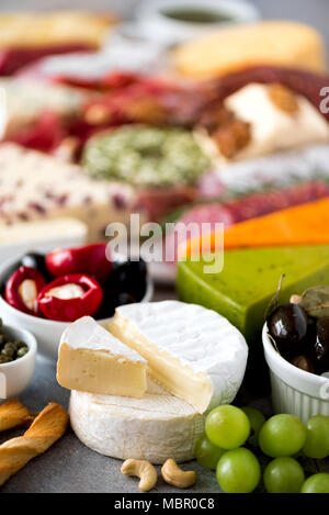 Assortment of hard, semi-soft and soft cheeses with olives, grissini bread sticks, capers, grape, on grey concrete backgound. Top view, copy space, flat lay. Cheese selection appetizer plate. - Stock Photo