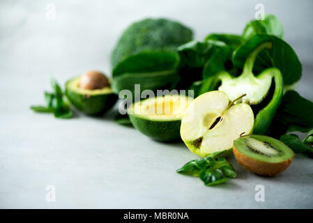 Green smoothie in glass jar with fresh organic green vegetables and fruits on grey background. Spring diet, healthy raw vegetarian, vegan concept, detox breakfast, alkaline clean eating. Copy space - Stock Photo