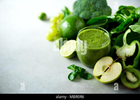 Glass with green health smoothie, kale leaves, lime, apple, kiwi, grapes, banana, avocado, lettuce. Copy space. Raw, vegan, vegetarian, alkaline food concept. - Stock Photo