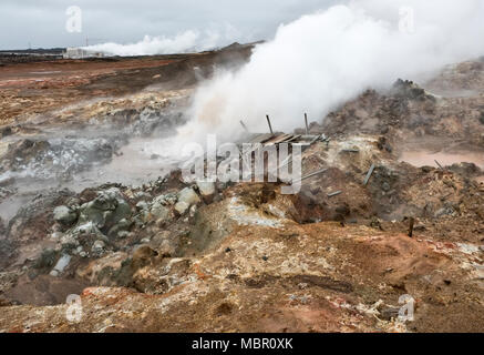 The Reykjanes peninsula, Iceland. A boiling mud pool in the Gunnuhver volcanic area. The Suðurnes geothermal power plant is in the background - Stock Photo